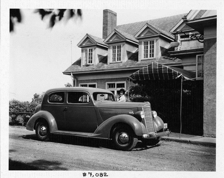 1937 Packard touring coupe parked on street in front of home