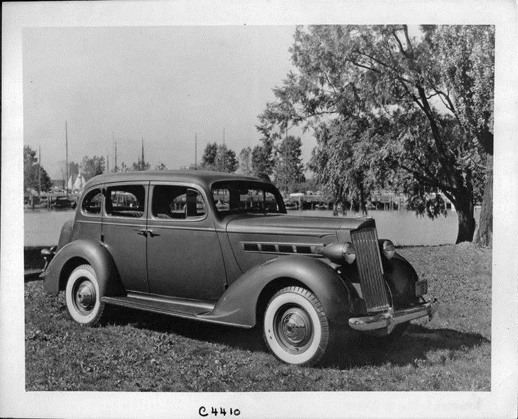 1937 Packard touring sedan, three-quarter right side view, parked on grass