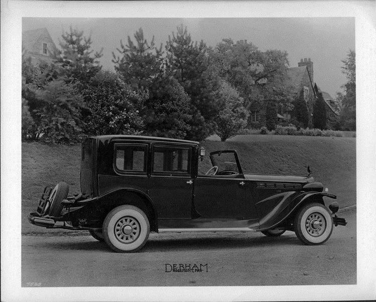 1937 Packard glass panel brougham, parked on road, house in background
