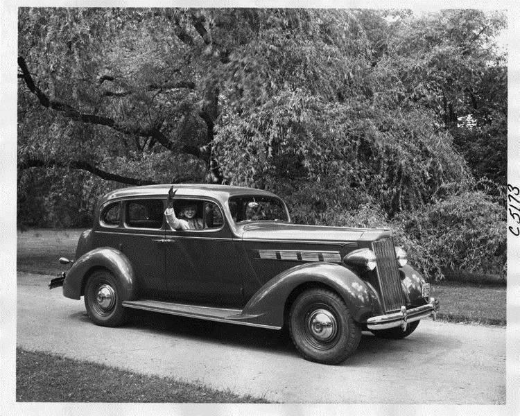 1937 Packard touring sedan parked on drive, female passenger waving