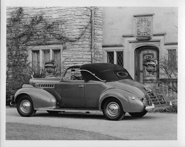 1939 Packard convertible coupe, top raised, parked in driveway of home