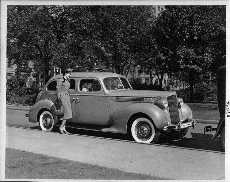 1939 Packard touring sedan parked on street, female at front passenger door