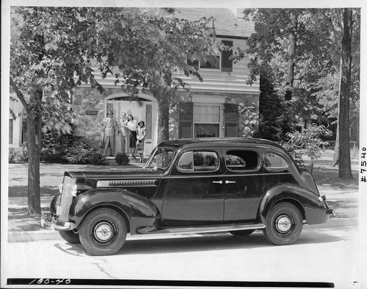 1939 Packard touring sedan, parked on street in front of house, family at front door