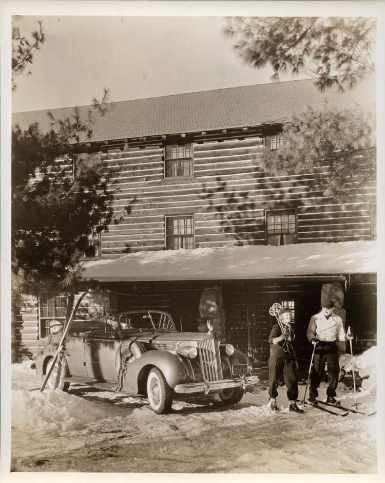 1939 Packard convertible sedan, top folded, couple in ski gear, ski lodge in background