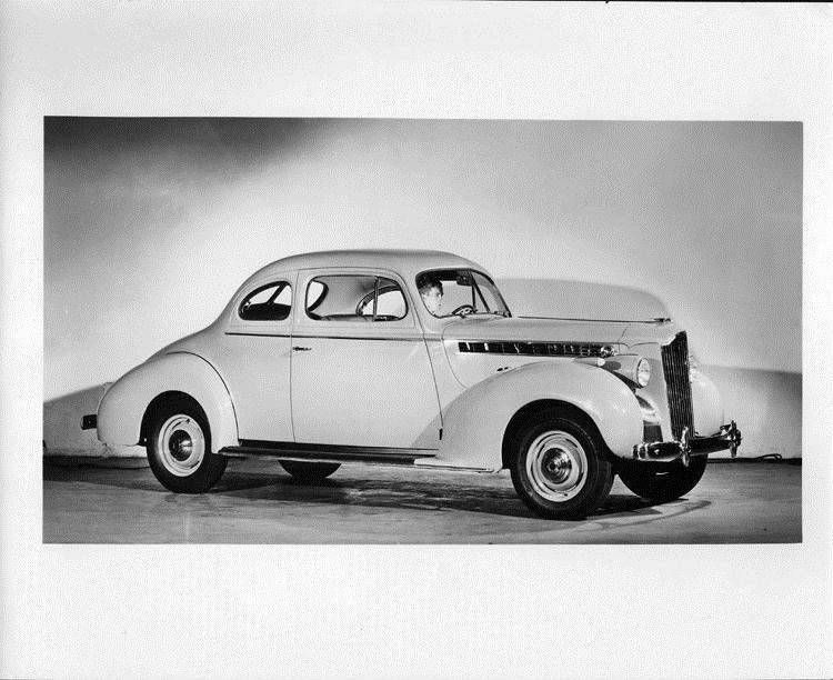 1940 Packard club coupe, nine-tenths right side view, male behind wheel