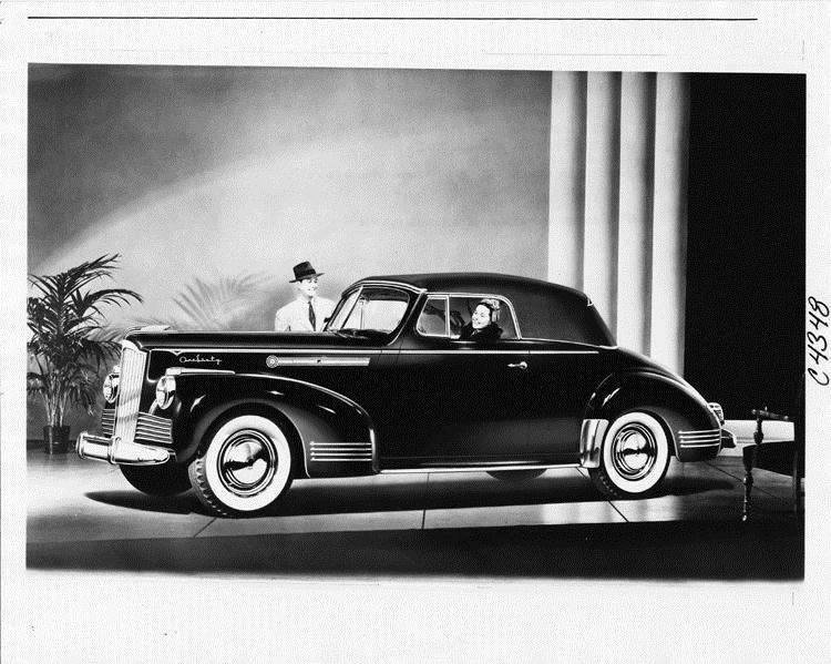 1942 Packard convertible coupe, top folded, female behind wheel, man standing at passenger door