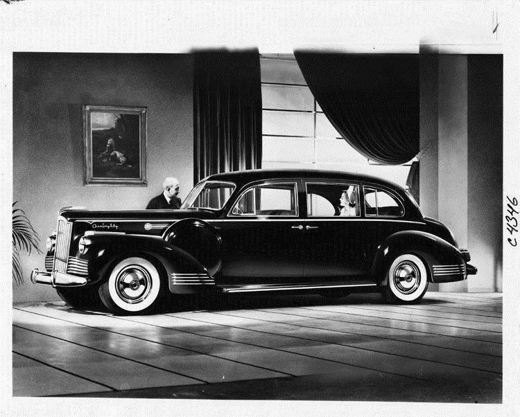 1942 Packard touring sedan, female passenger in rear, man standing at passenger door
