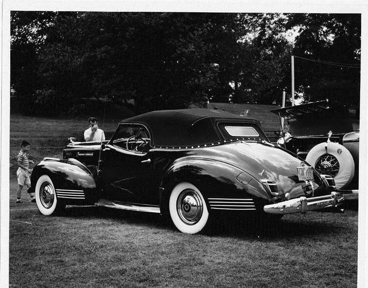 1942 Packard convertible victoria, three-quarter rear view, top raised, parked on grass