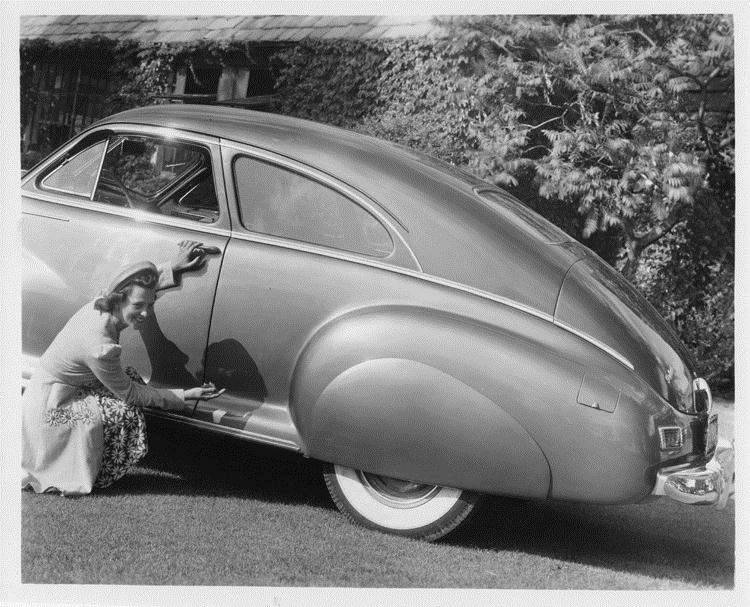 1942 Packard club sedan, female gesturing at car's features