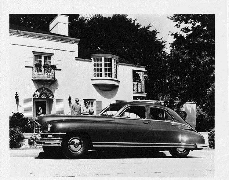 1948 Packard touring sedan, parked on street in front of home with couple