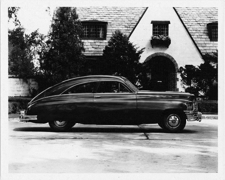 1948 Packard club sedan, right side view, parked on street in front of house