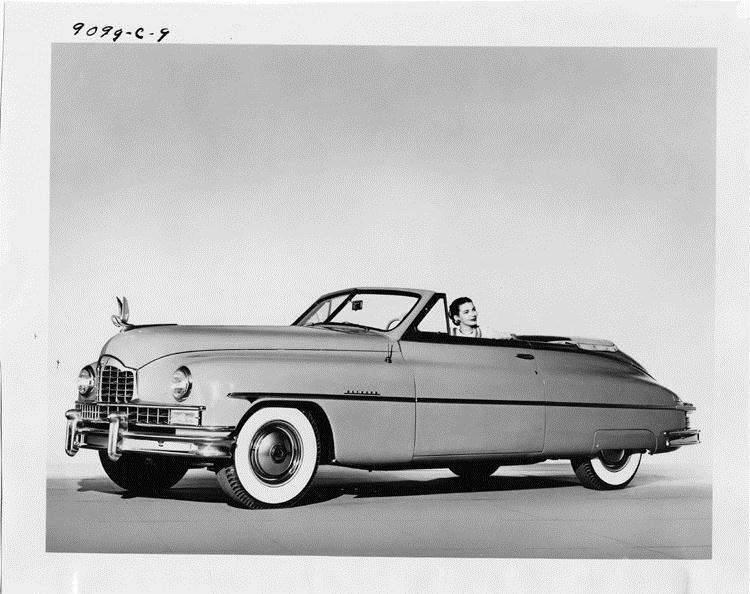 1949 Packard convertible, top folded, female behind wheel