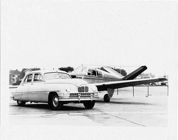 1949 Packard sedan parked on airstrip in front of single-engine airplane