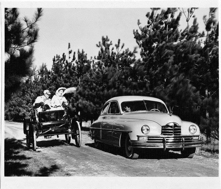 1949 Packard sedan, coming alongside 1899 Packard model A with two occupants