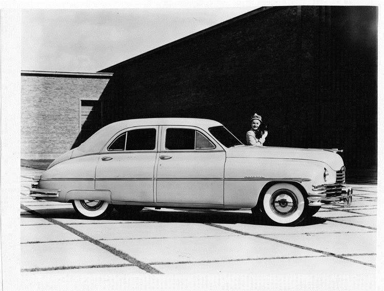 1949 Packard sedan, female holding a small dog standing near driver's door