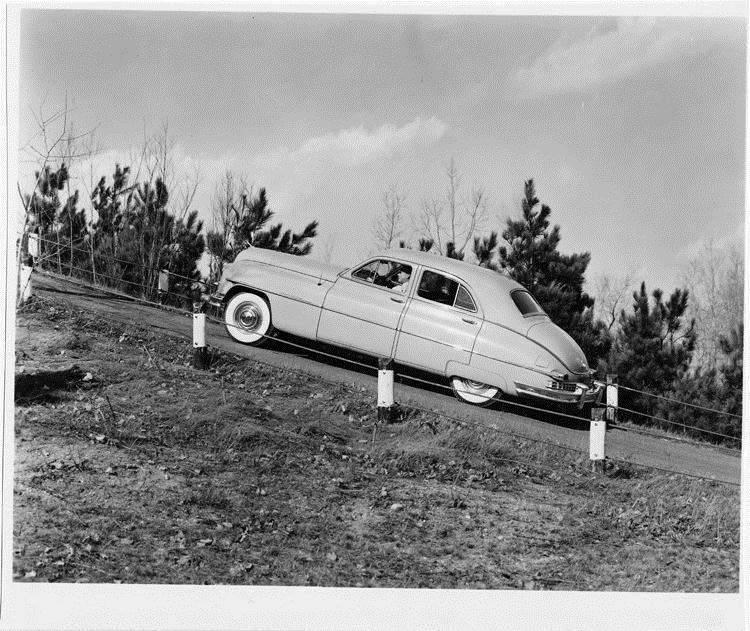 1949 Packard sedan, left side view, driving up steep hill, male behind wheel