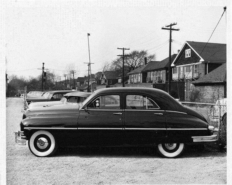 1949 Packard sedan, left side view, parked in lot, houses in background
