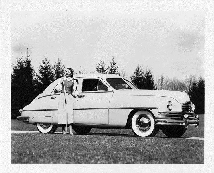 1949 Packard sedan, parked on grass, female standing at front passenger door