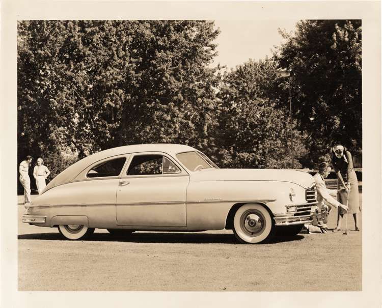 1949 Packard club sedan, parked on grass, couple with golf club at front of car