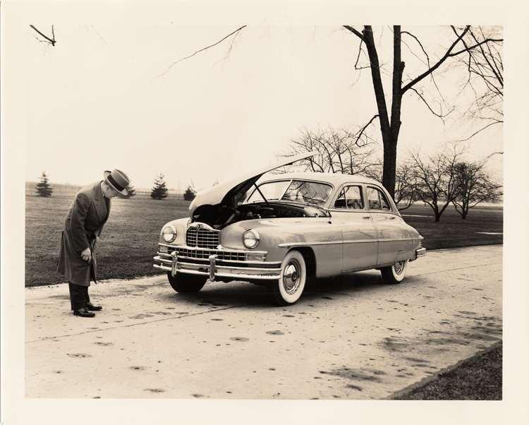 1950 Packard sedan, hood raised, man inspecting front of car