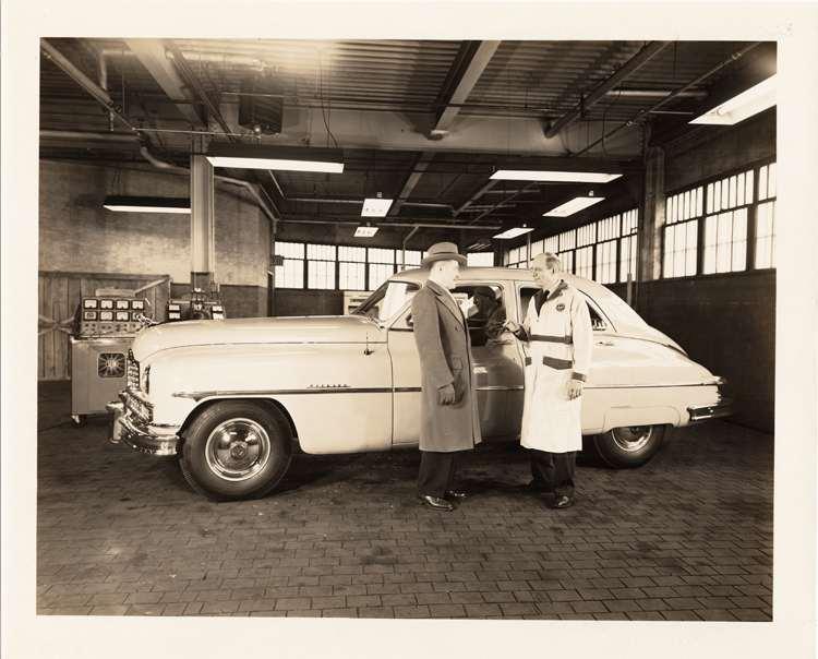 1950 Packard sedan, left side view, Mike Kollins & T.W. Nerthey standing at driver's door