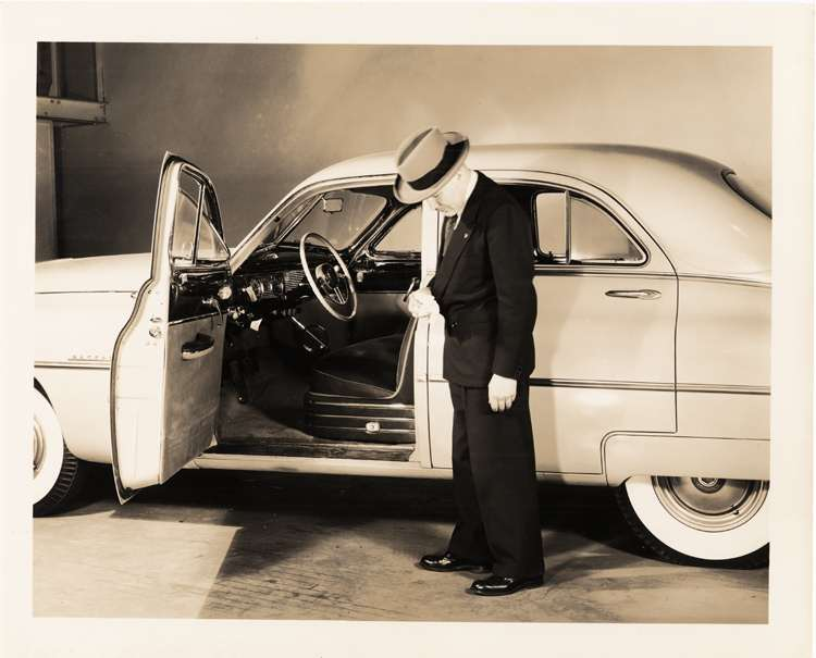 1950 Packard custom sedan, left side view, Mike Kollins standing at open driver's door