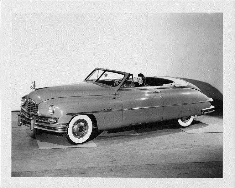 1950 Packard custom convertible, top folded, female behind wheel
