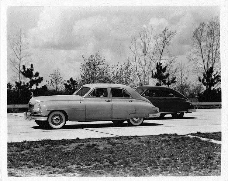 1950 Packard sedans, male drivers, parked on drive