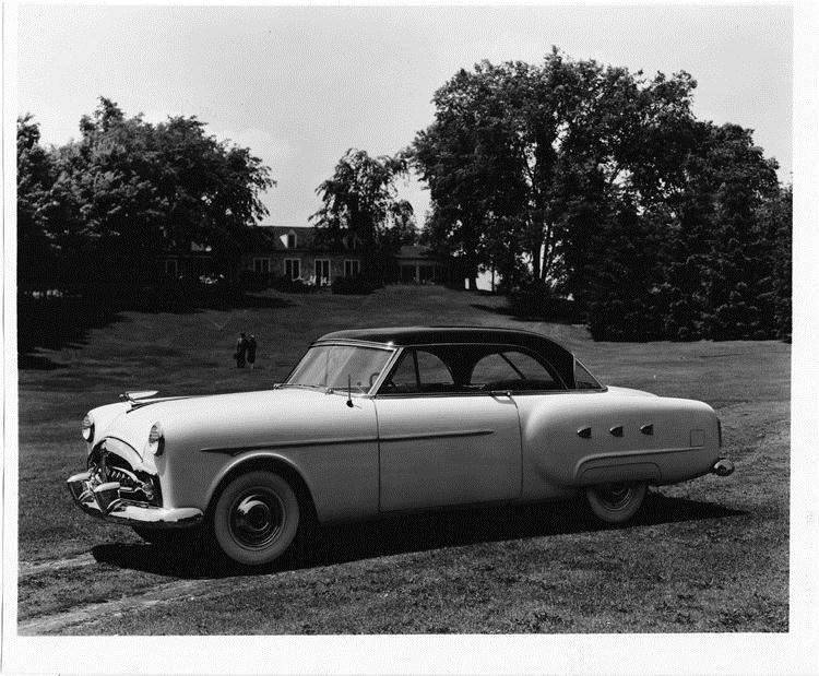 1952 Packard Mayfair, parked on grass, couple walking from house in background