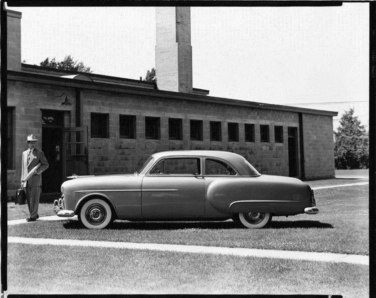 1951 Packard 200 sedan, parked on grass in front of building, man standing nearby