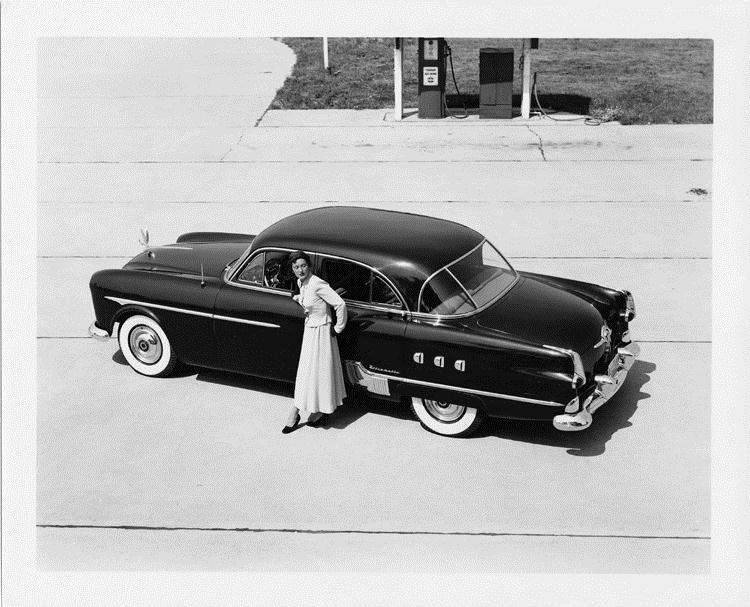 1951 Packard Patrician 400 parked near gas pump with stylish woman