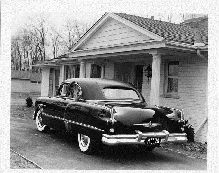1953 Packard formal sedan, parked in driveway in front of house