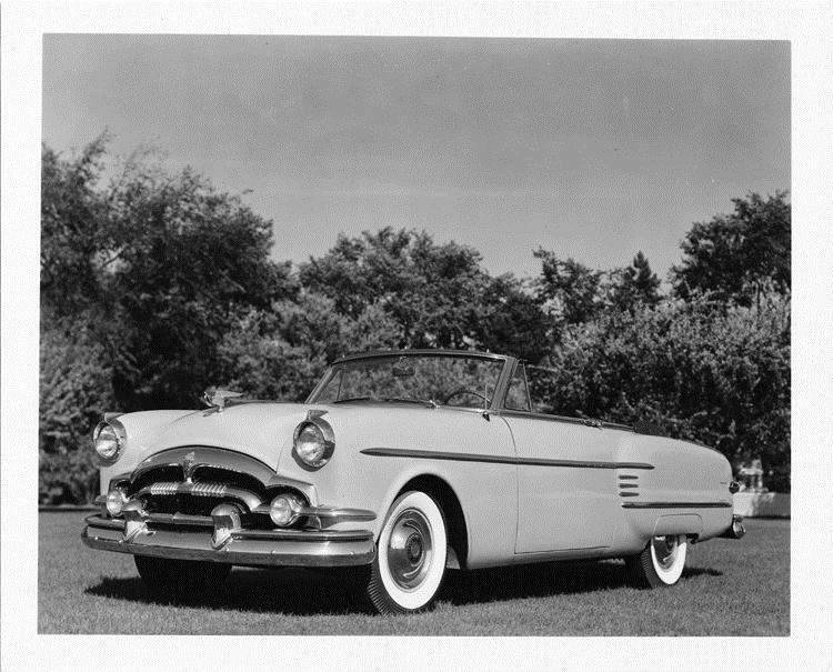 1954 Packard convertible coupe, three-quarter front left view, top folded, parked on grass