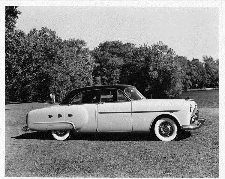 1952 Packard touring sedan, right side view, parked on grass, couple in background