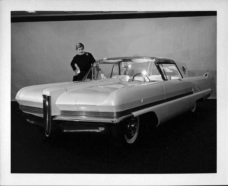 1956 Packard Predictor, three-quarter front view, female standing at passenger side