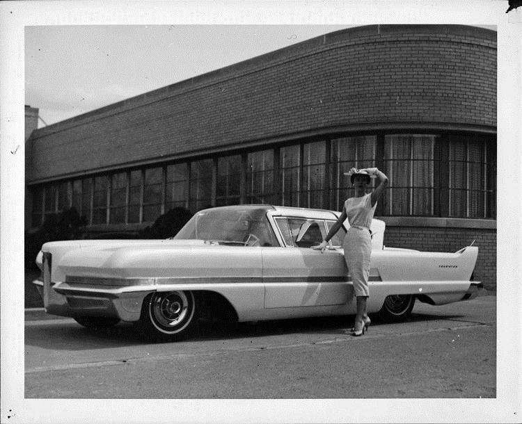 1956 Packard Predictor, female standing at driver's door, parked on street by brick building