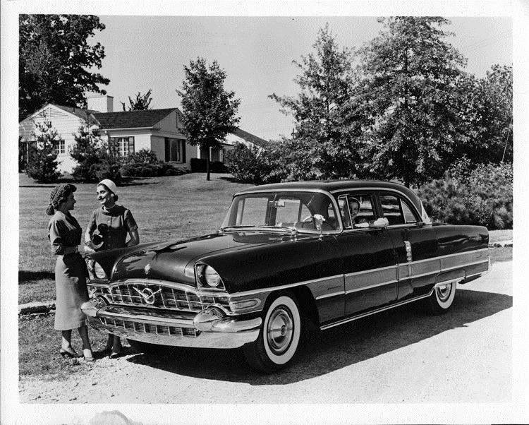 1956 Packard 2-door sedan, female behind wheel, two females standing at front passenger side