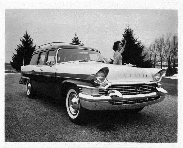 1957 Packard station wagon, female standing at driver's door