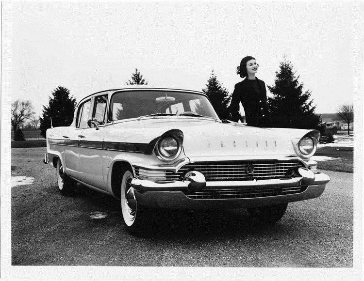 1957 Packard Clipper sedan, three-quarter front view, female standing at driver's door