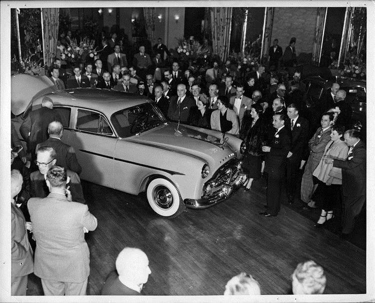 1951 Packard 4-door sedan admired by crowd at automobile show