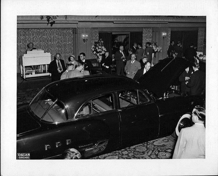 1951 salon showing a 1951 Packard 4-door sedan, crowd surrounding car