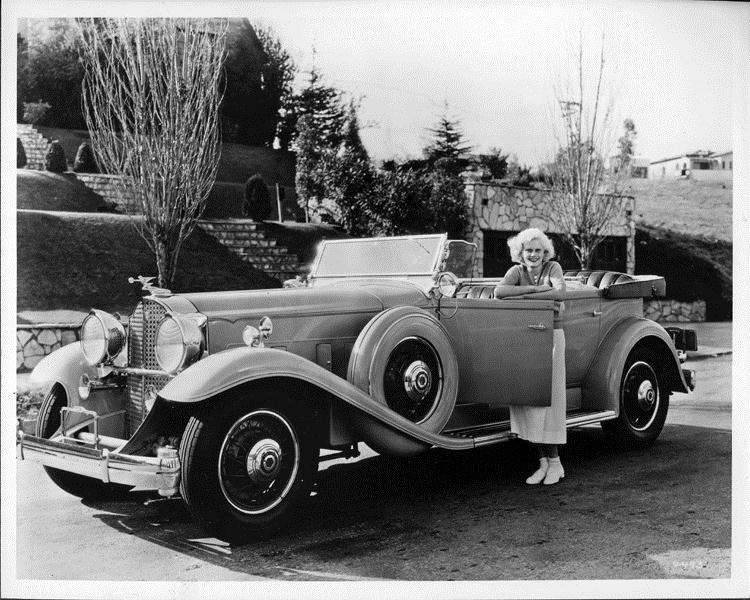 1932 Packard sport phaeton and owner actress Jean Harlow leaning on open driver's door