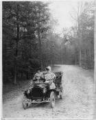 1907 Packard 30 Model U with two passengers in the woods