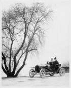 1907 Packard 30 Model U runabout with two passengers in winter by tree