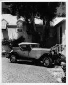 1929 Packard runabout, seven-eights left front view, top raised, parked in driveway, house in backgr