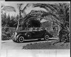 1936 Packard convertible victoria pulling out of drive with palms
