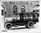 1914 Packard truck, left side view, parked on street in front of W.S. Seaman Company building